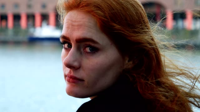 Portrait of young red haired lady looking at camera over shoulder video