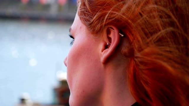 Portrait of young red haired lady looking out to sea, sadness or loneliness video