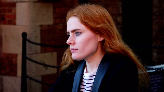 Portrait of young redhaired lady looking off camera video