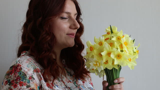 Portrait of young romantic smiling beautiful woman girl sniffing smelling yellow daffodils flowers in bouquet