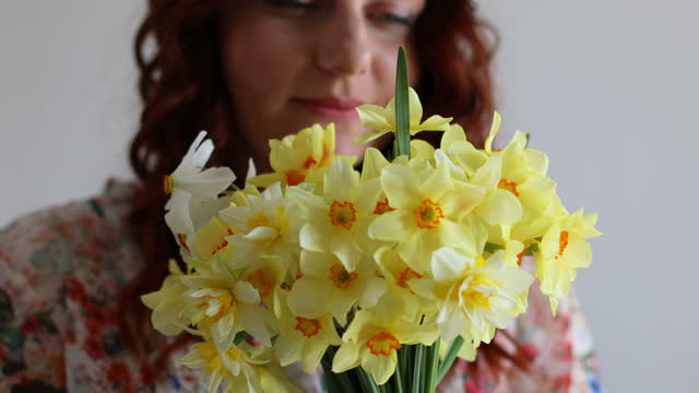 Portrait of young romantic woman smelling spring yellow daffodils flowers in bouquet at home. 4k