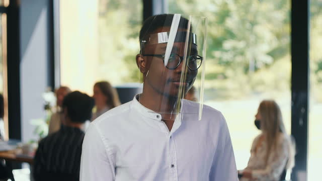 Portrait of young serious 20s African office manager man wear plastic face shield nodding at light workplace slow motion