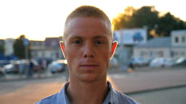 portrait of young serious businessman in shirt looking into the camera against the background of cars parking on sunset. close up of confident successful man standing at urban environment. - только один мужчина стоковые видео и кадры b-roll