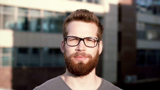 Portrait of young serious man with beard and glasses standing in front of sun, linking. Businessman stands near office video