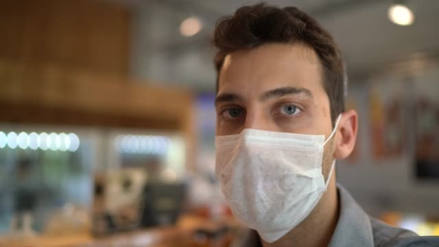 Portrait of young small business man owner with face mask video