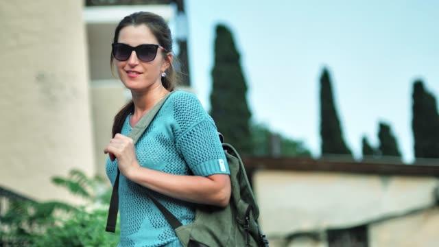 portrait of young smiling female traveler in sunglasses medium shot - viaggiare zaino in spalla video stock e b–roll
