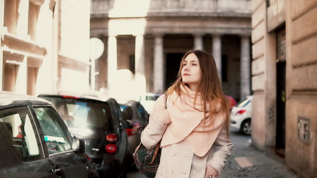 Portrait of young stylish woman walking in the city centre. Inspired and happy girl explores the old streets of the city video