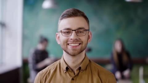 porträt des jungen erfolgreicher geschäftsmann im geschäftigen büro. gut aussehend männlichen mitarbeiter blick in die kamera und lächelnd - junge männer stock-videos und b-roll-filmmaterial