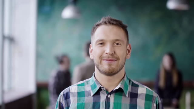 portrait of young successful businessman at busy office. handsome male employee looking at camera and smiling. slow mo - men filmów i materiałów b-roll