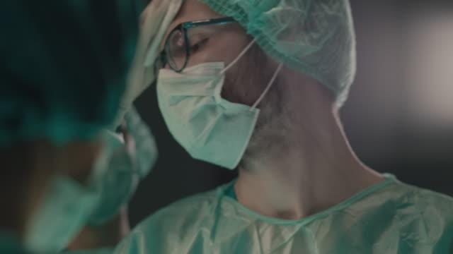 cerrahi operasyon yapan genç cerrahın portresi - cerrahi ekipman stok videoları ve detay görüntü çekimi