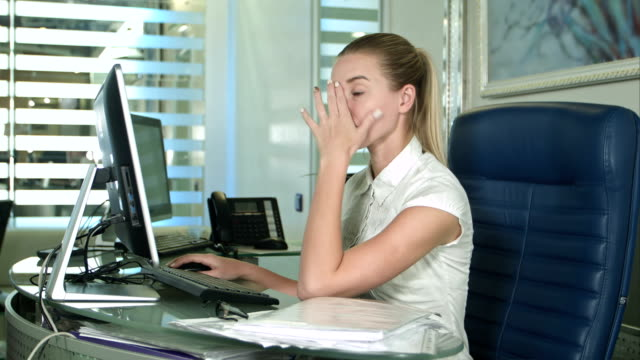 Portrait of young unhappy business woman at desk in office video