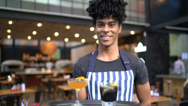 Portrait of young waiter holding a tray with a few drinks Portrait of young waiter holding a tray with a few drinks wait staff stock videos & royalty-free footage