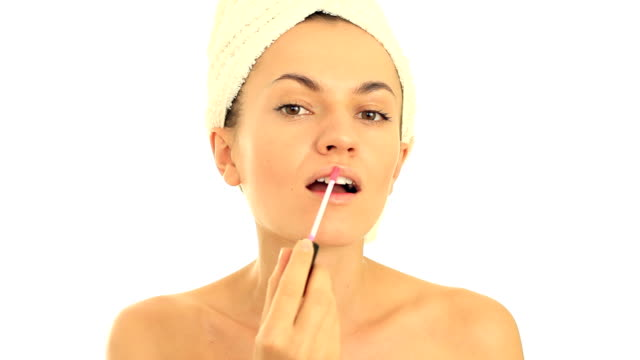 Portrait of young woman applying lip gloss, isolated on white video
