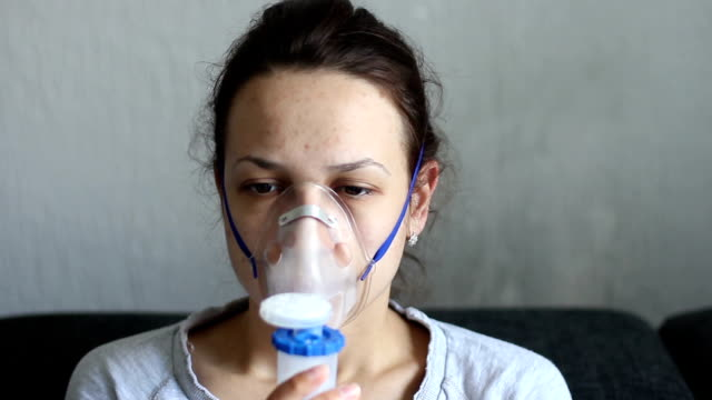portrait of young woman doing inhalation at home video