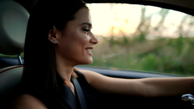 portrait of young woman driving car - close up auto video stock e b–roll