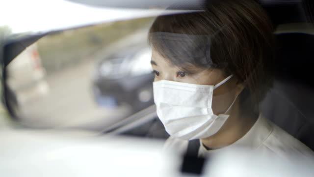 stockvideo's en b-roll-footage met portret van jonge vrouw die auto met masker drijft - mirror mask