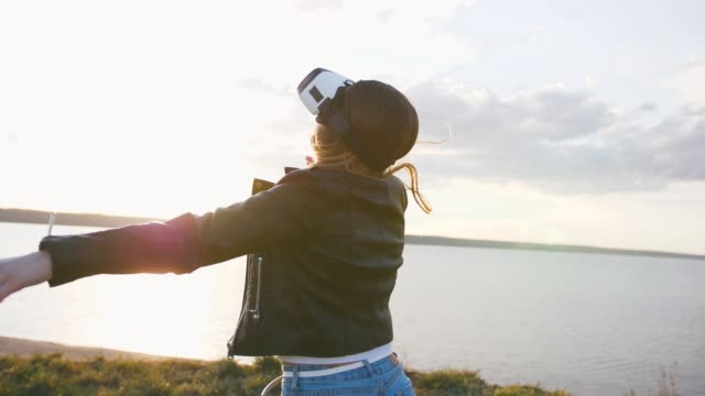 portrait of young woman having some fun in vr glasses outdoors with beatiful sea sunset background, slow motion - ritratto 360 gradi video stock e b–roll