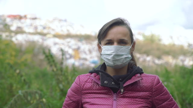 Portrait of Young Woman in a Mask near a Landfill