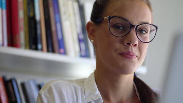 Portrait of Young Woman in Library Potting Down Eyeglasses and Looking at Camera video