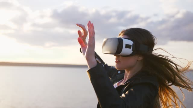 portrait of young woman in vr glasses outdoors with beatiful sea sunset background, slow motion - ritratto 360 gradi video stock e b–roll