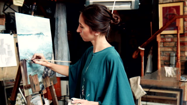 Portrait of young woman painting a canvas in a studio video