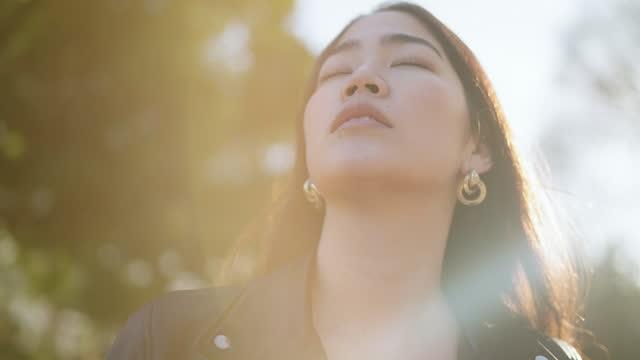 ritratto di giovane donna rilassante con gli occhi chiusi nella natura - ambientazione tranquilla video stock e b–roll