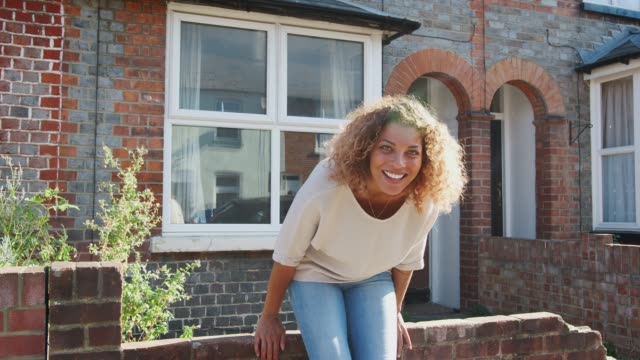 Portrait Of Young Woman Sitting On Wall Outside New Home In Urban Street Proud young woman sitting on wall outside new home smiling at camera - shot in slow motion home ownership stock videos & royalty-free footage