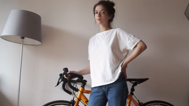 Portrait of young woman standing near bike indoors Portrait of young woman standing near bike indoors before riding. Sportive girl poses looking to camera holding bicycle ready to ride. Sport adventure racing cycling lifestyle handlebar stock videos & royalty-free footage