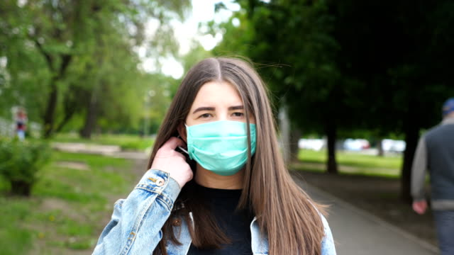 портрет молодой женщины снимает медицинскую маску и серьезно смотрит в камеру. девушка снимает защитную маску с вируса covid-19 на открытом во� - удалять стоковые видео и кадры b-roll