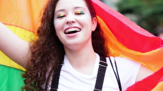 vídeos de stock, filmes e b-roll de retrato de uma jovem mulher acenando uma bandeira de arco-íris - homossexualidade