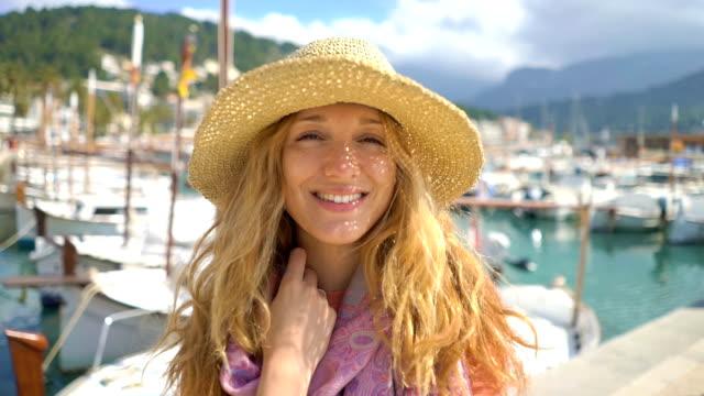 vídeos de stock, filmes e b-roll de retrato do chapéu de palha desgastando da mulher nova que sorri na câmera com fundo do seacoast. - marina