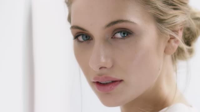 vídeos de stock, filmes e b-roll de retrato de uma jovem mulher com lindos olhos azuis - skincare