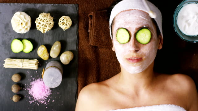 Portrait of young woman with facial mask and cucumber treatment on her face have a relax in a wellness center. Concept of skincare, cosmetics, beauty salon, facial treatment, facial massage, wellbeing video