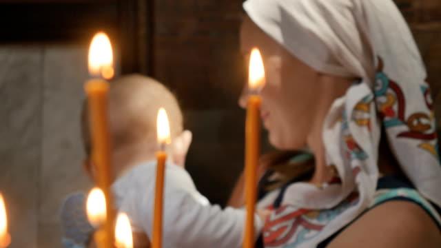 vidéos et rushes de portrait de jeune femme avec petit garçon derrière les cierges à l'église - baptême