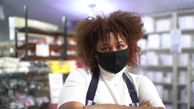 vídeos de stock e filmes b-roll de portrait of young woman working at store - wearing face mask - afro latino mask