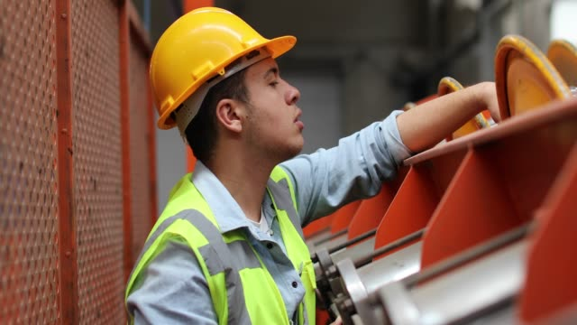 Portrait of young worker man working with ball valves in factory