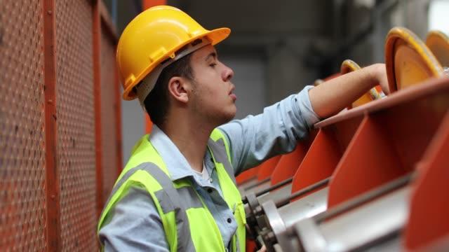 porträtt av ung arbetare man arbetar med kulventiler i fabriken - värmepump bildbanksvideor och videomaterial från bakom kulisserna