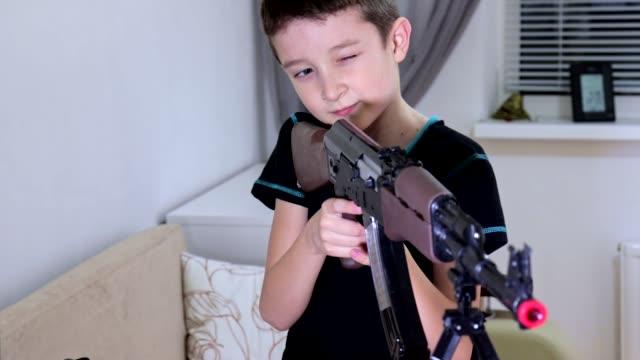 Portrait preteen boy playing and shooting automatic weapon gun riffle Kalashnikov at home