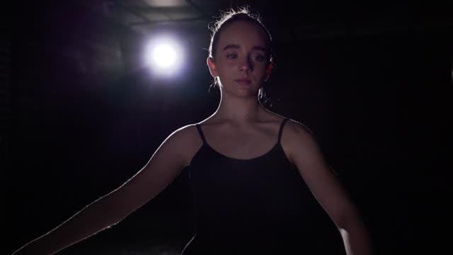 porträt-professionelle niedlich ballett-tänzerin im rampenlicht auf schwarzem hintergrund im studio stehen. ballerina zeigt klassisches ballett pas. slow-motion. - ballettschuh stock-videos und b-roll-filmmaterial