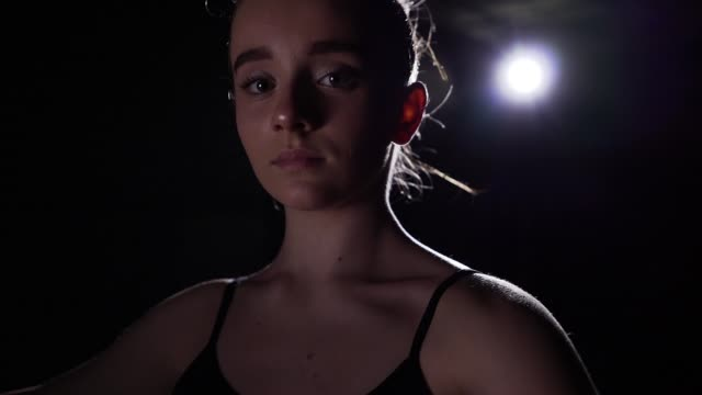スタジオで黒の背景に注目を浴びて立っている肖像画プロの若いバレリーナ。バレエ ダンサーは、クラシック バレエのパを示しています。スローモーション。 - バレリーナ点の映像素材/bロール