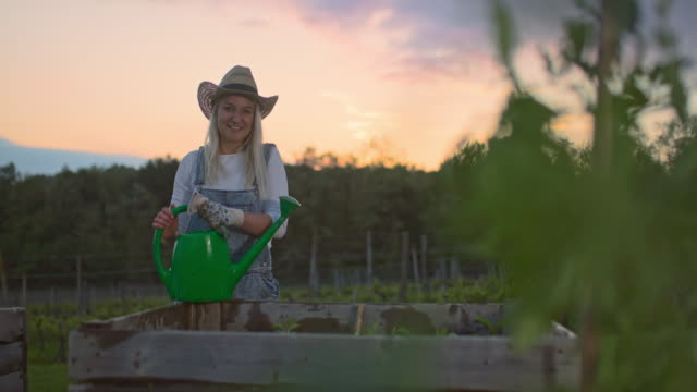 MS Portrait satisfied woman with watering can gardening at raised bed