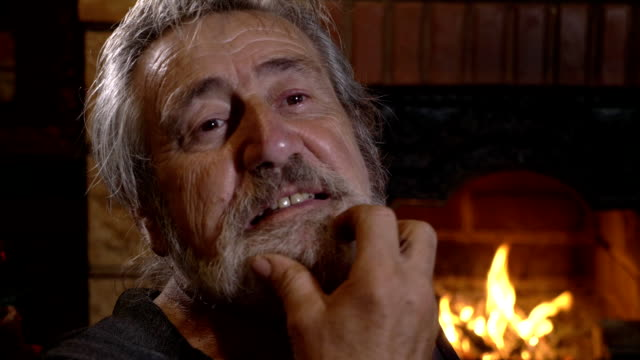 Portrait senior man alone at home near the fireplace video