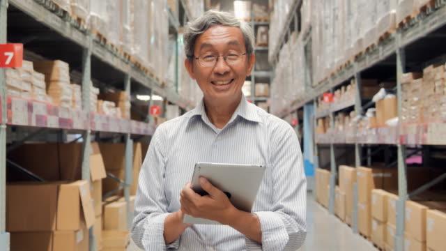 カメラを見て、倉庫でタブレットを持っている肖像画の先輩男性。スマート倉庫管理システム。倉庫,技術,人,イノベーション,リーダーシップ,ビジネス,ファイナンス,成功,退職,交通,オンライ - 通販点の映像素材/bロール