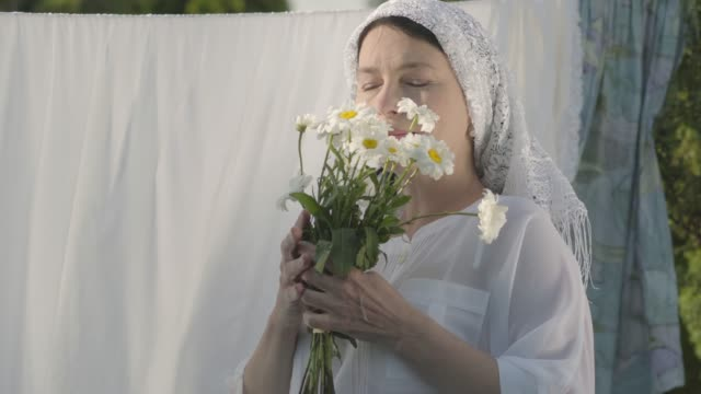 Portrait senior woman with white shawl on her head sniffing daisies looking at camera near the clothesline outdoors.