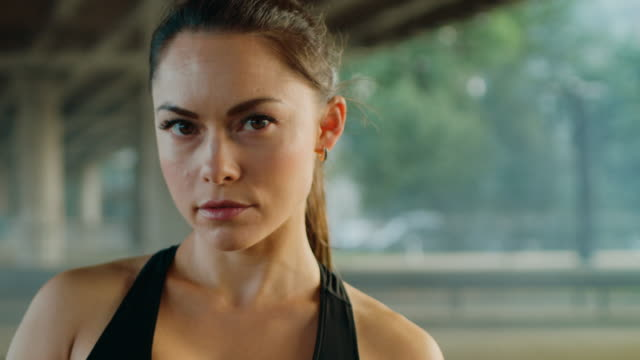 portrait shot of a beautiful confident fitness girl in black athletic top on a street. she is a brunette with brown eyes with her hair tied in an ponytail. shot is taken in an urban environment with cars in the background. - decolleté video stock e b–roll