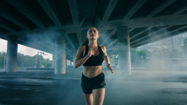 portrait shot of a beautiful confident fitness girl in black athletic top and shorts jogging through a smoky street. she is running in an urban environment under a bridge with cars in the background. - decolleté video stock e b–roll