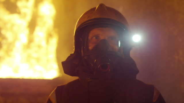 Portrait Shot of a Brave Fireman Standing in a Burning Building Fire Raging Behind Him. Open Flames and Smoke in the Background. - Vidéo