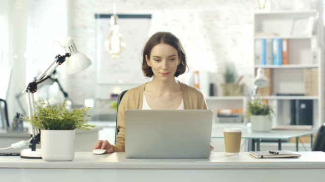 Portrait Shot of a Creative Woman Sitting at Her Desk. Using Notebook. She Sits in a Light and Modern Office.