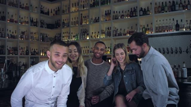 vídeos de stock, filmes e b-roll de tiro do retrato de um grupo de amigos sorrindo para a câmera em um bar - costumer