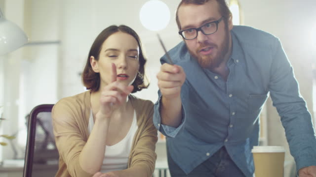 Portrait Shot of a Man and a Woman Discussing Work Looking Streight at the Camera. They are in the Brightly Lit Modern Office. video